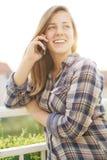 Chica joven que manda un SMS en el teléfono Foto de archivo libre de regalías
