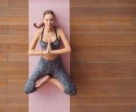 Chica joven que medita en clase de la yoga Foto de archivo libre de regalías