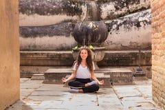Chica joven que medita en la posición de la yoga en un templo budista foto de archivo libre de regalías