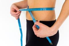 Chica joven que mide su cintura Imagen de archivo