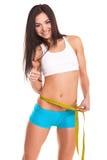 Chica joven que mide su cintura y que es feliz Fotografía de archivo libre de regalías