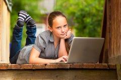 Chica joven que miente con un ordenador portátil Fotografía de archivo libre de regalías