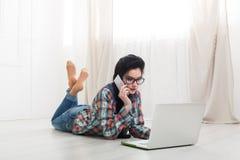 Chica joven que miente con una computadora portátil Fotos de archivo