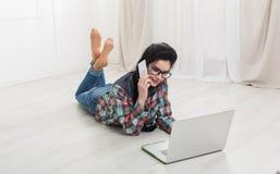 Chica joven que miente con una computadora portátil Imagenes de archivo