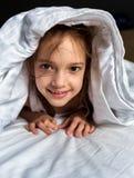 Chica joven que miente debajo de la manta Foto de archivo libre de regalías
