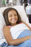 Chica joven que miente en cama de hospital Imagen de archivo