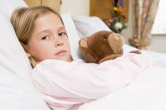 Chica joven que miente en cama de hospital con el oso del peluche Fotografía de archivo