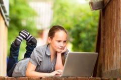 Chica joven que miente en el pórtico de la casa con una computadora portátil. Foto de archivo