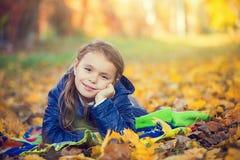 Chica joven que miente en el parque Foto de archivo libre de regalías