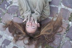 Chica joven que miente en el pavimento de piedra con el pelo dispersado foto de archivo libre de regalías