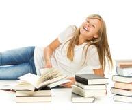 Chica joven que miente en el piso con los libros Foto de archivo