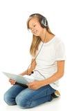Chica joven que miente en el piso que escucha la música Fotos de archivo