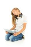 Chica joven que miente en el piso que escucha la música sobre la parte posterior del blanco Fotos de archivo libres de regalías