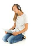 Chica joven que miente en el piso que escucha la música sobre la parte posterior del blanco Fotografía de archivo