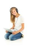 Chica joven que miente en el piso que escucha la música sobre la parte posterior del blanco Imágenes de archivo libres de regalías