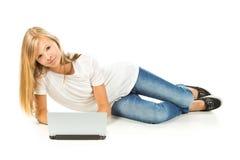Chica joven que miente en el piso usando el ordenador portátil Fotos de archivo libres de regalías