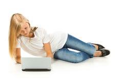 Chica joven que miente en el piso usando el ordenador portátil Fotos de archivo