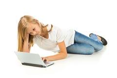 Chica joven que miente en el piso usando el ordenador portátil Imagenes de archivo