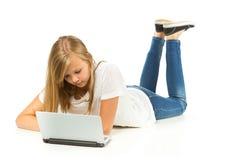 Chica joven que miente en el piso usando el ordenador portátil Imágenes de archivo libres de regalías