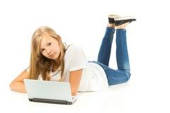 Chica joven que miente en el piso usando el ordenador portátil Fotografía de archivo
