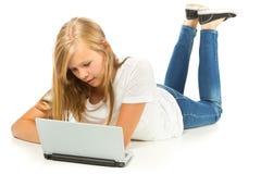 Chica joven que miente en el piso usando el ordenador portátil sobre el fondo blanco Fotos de archivo libres de regalías