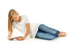 Chica joven que miente en el piso usando la PC de la tableta sobre el backgro blanco Fotografía de archivo