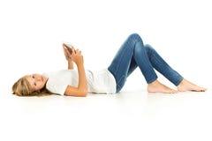 Chica joven que miente en el piso usando la PC de la tableta sobre el backgro blanco Imagenes de archivo