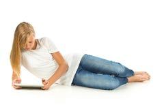 Chica joven que miente en el piso usando la PC de la tableta sobre el backgro blanco Fotos de archivo libres de regalías