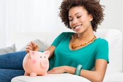 Mujer que pone la moneda en Piggybank Foto de archivo libre de regalías