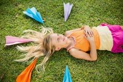 Chica joven que miente en hierba alrededor de los aviones de papel Fotos de archivo libres de regalías