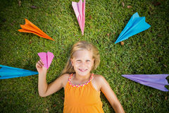 Chica joven que miente en hierba alrededor de los aviones de papel Imagenes de archivo