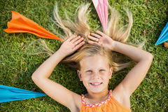 Chica joven que miente en hierba alrededor de los aviones de papel Foto de archivo