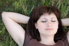 Chica joven que miente en hierba con los ojos Imagen de archivo libre de regalías