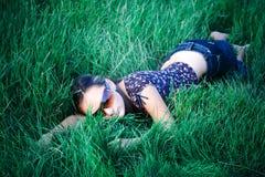 Chica joven que miente en hierba verde Foto de archivo