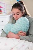 Chica joven que miente en la cama que abraza el amortiguador en forma de corazón Fotos de archivo libres de regalías
