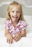 Chica joven que miente en la cama que tira de la cara divertida Imagenes de archivo