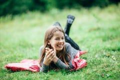 Chica joven que miente en la chaqueta rosada en prado verde Imagen de archivo
