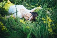 Chica joven que miente en la hierba Fotos de archivo libres de regalías