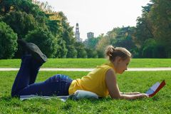Chica joven que miente en la hierba en el parque y que lee un periódico Imagen de archivo