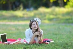 Chica joven que miente en la hierba en el parque y los trabajos en un ordenador portátil Foto de archivo