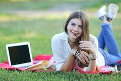 Chica joven que miente en la hierba en el parque y los trabajos en un ordenador portátil Imágenes de archivo libres de regalías