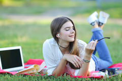 Chica joven que miente en la hierba en el parque y los trabajos en un ordenador portátil Fotografía de archivo