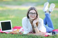 Chica joven que miente en la hierba en el parque y los trabajos en un ordenador portátil Foto de archivo libre de regalías