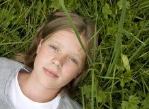 Chica joven que miente en la hierba que soña con? Fotos de archivo