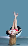 Chica joven que miente en la silla al revés Fotos de archivo