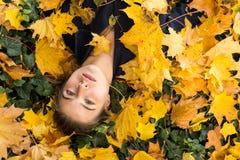 Chica joven que miente en las hojas del amarillo del otoño Imágenes de archivo libres de regalías