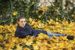 Chica joven que miente en las hojas en el parque del otoño Imagen de archivo libre de regalías