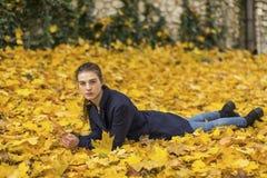 Chica joven que miente en las hojas en parque del otoño Fotos de archivo libres de regalías