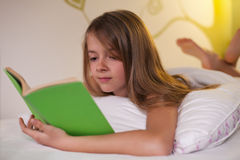 Chica joven que miente en su vientre en la cama - lectura de un libro, d baja Fotos de archivo libres de regalías