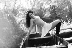 Chica joven que miente en un barco que flota en el lago Foto de archivo
